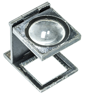 Abra Marketing's design production benefits our clients. Photo of an old, worn printer's loupe.